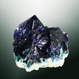 Azurita Tsumeb, Tsumeb (constituencia), Otavi (mts.), Oshikoto (región), Namibia. Tsumeb (m). 1,7 x 1,8 x 1,4 cm. (ejemplar) / 1,2 x 1,0 x 0,2 cm. (cristal pral.) Cristales prismátics aplananados, uno de ellos claramente dominante, transparentes, en matriz. Ejemplar de 1985. (Autor: Carles Curto)
