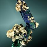 Azurita Touissit, Oujda-Angad (pref.), L'Oriental (wilaya), Marruecos. Zelidja (m). 4,6 x 3,8 x 2,5 cm. 8ejemplar) / 3,3 x 1,2 x 0,7 cm. (cristal pral.) Agregado de dos cristales prismáticos biterminados, en matriz, con malaquita pseudomórfica y pequeños cristales maclados de cerusita. Ejemplar de 1989 (Autor: Carles Curto)