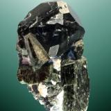 Espinela (pleonasta) Hatimi, Sakha (Iakutsk), República de Sakha (Iakutia), Rusia. 7,6 x 4,6 x 4,9 cm. (ejemplar) / 4,2 x 4,1 x 4,4 cm. (cristal) Cristal equidimensional complejo, con el octaedro dominante, negro, sobre un cristal de diópsido cromífero. Ejemplar de 1992. (Autor: Carles Curto)