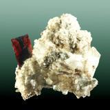 Brookita Pashine, Kharan, Baluchistan, Pakistan. Ras-Koh. 4,0 x 4,5 x 4,3 cm. (ejemplar) / 1,6 x 0,9 x 0,1cm. (cristal) Cristal prismático aplanado, transparente con inclusiones zonadas negras. En matriz con cuarzo y albita. Ejemplar de 2009 (Autor: Carles Curto)