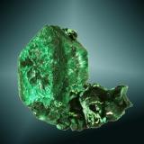 Malaquita psudomórfica de azurita Tsumeb, Tsumeb (constituencia), Otavi (mts.), Oshikoto (región), Namibia. Tsumeb (m). 3,3 x 3,3 x 2,6 cm. (ejemplar) / 3,1 x 2,3 x 1,1 cm. (cristal) Agregado de cristales pseudomórficos de azurita, uno de ellos claramente dominante, biterminado, con pequeños cristales de azurita. Ejemplar de 1982. (Autor: Carles Curto)