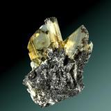 Anglesita Touissit, Oujda-Angad (pref.), L'Oriental (wilaya), Marruecos. Zelidja (m). 3,4 x 2,8 x 2,2 cm. (ejemplar) / 1,6 x 1,2 x 0,4 cm. (cristal pral.) Cristales prismáticos amarillos y  transparentes, en matriz de galena. Ejemplar de 1979. (Autor: Carles Curto)