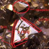 Pirita Distrito de Julcani, Provincia de Angaraes, Departamento de Huancavelica, Perú 6,5 x 4,5 x 2,5 cm. Índices de Miller dibujados sobre un octaedro de la pieza anterior. Aparecen las caras del octaedro (111), rombododecaedro (110) y trapezoedro (211) -dos pequeñas caras al final de los rombododecaedros-. Señalado con un círculo sobre un octaedro las líneas de crecimiento de lo que iba a ser un triaquisoctaedro (una pirámide que tiene como base dicha cara del octaedro). Ver foto de Mindat citada. (Autor: Antonio Alcaide)