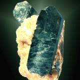 Fluorapatito Slyudianka, Irkutskaya (oblast), Baykal, Rusia. 5,4x3,2x3,2 cm. / 3,9x1,5x1,4 cm. (cristal pral.) Dos cristales prismáticos biterminados, de color azul intenso, en matriz de calcita naranja. Ejemplar de 1996. (Autor: Carles Curto)