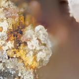 Celestine, Titanite, Pyrite Poudrette quarry (Demix quarry; Uni-Mix quarry; Desourdy quarry; Carrière Mont Saint-Hilaire), Mont Saint-Hilaire, Rouville RCM, Montérégie, Québec, Canada FOV=2mm Celestine is fine mass of white and yellowish crystals and the titanite is the pink crystal masses. (Author: Doug)