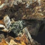 Cuprita malaquitizada y Ankerita. Zanja abandonada. Pardos. Guadalajara. Castilla la Mancha. España. 20 x 15 mm (Encuadre aproximado de la foto) Recolectada en 1997. Cerca de La mina Estrella, existian unas zanjas abandonadas donde se había extraido parte de la montera de alteración de las dolomías ricas en hierro (limonita). En las geodas de Dolomita y Ankerita, aparecían cristales de presunta Cuprita (lo dedujimos por su morfología) pseudomorfizados por Malaquita. (Autor: Daniel Agut)