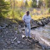 """Using the metal detector to locate """"treasures"""" at an old mine site. The fencing that you see in the background is to protect against falling into an open hole. Many of the very rich silver veins were exposed on surface and mined out completely. (Author: Joseph D'Oliveira)"""