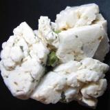Titanita y ortoclasa Imilchil, Alto Atlas, Marruecos 5 x 5 cm. Pequeños cristales verdes de titanita entre los cristales de un agregado de prismas pseudohexagonales de ortoclasa (feldespato potásico). (Autor: prcantos)