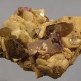Fluorite, Topaz, Microcline, Smoky Quartz, Albite. Lundy Island, Devon, England, UK 60mm x 58mm x 21mm A real mixture of minerals from a small pegmatitic pocket in the granite. The purple fluorite takes the form of an elongated cube with one face 16mm long, though not without damage.  Topaz crystal lying flat on the microcline is 8 x 4mm.  The tiny little 'starbursts' of black acicular crystals on the micrcline - I'm fairly certain these are tourmaline var. schorl. (Author: Mike Wood)