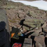 This was my bed for the night before, on a mat in a bivi bag in a rocky niche. I was planning on sleeping on a nice grassy spot around the corner but the wind got up and it was cold, so I moved here for shelter. It was more comfortable than it looks! (Author: Mike Wood)
