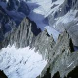 Photo taken from approx. 4,000m on the south arete (ridge) of the Aiguille Verte, looking down at the Aiguille du Moine (3412m) at the end of the arete; where in 1991 I found some crystals! The stripy glacier is the famous Mer de Glace.  Photo taken August 1992, by me : ) Scanned from slide photo. (Author: Mike Wood)