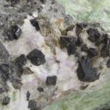 Steenstrupine-(Ce) xx  Ilímaussaq intrusion, Narsaq, S-Greenland section from piece on the previous photo, crystals around 0,5 x 0,5 cm (Author: kakov)