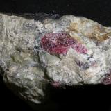 Eudialyte Kola Peninsula, Rusia 9 x 6 x 4 cm The other side of the same piece (with dark matrix) on the next photo.   This is one of the classic minerals of alkaline sites. It looks like garnet but have a completely different composition and structure, its hardness is also considerably lower than garnet. (Author: kakov)