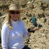 Ronna Jewett, discoverer of the mondo best pocket holding a small quartz from her find.  The pocket exceeded 4 feet (1.3 m) in depth by the time it was finished. (Author: Tony L. Potucek)