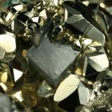 Beryl (variety emerald), Calcite and Pyrite<br />Chivor mining district, El Acuario Mine, Municipio Chivor, Eastern Emerald Belt, Boyacá Department, Colombia<br />Dolomite rhomb ~1cm<br /> (Author: Fiebre Verde)