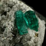 Beryl (variety emerald), Calcite, Pyrite<br />Chivor mining district, El Oriente Mine, Municipio Chivor, Eastern Emerald Belt, Boyacá Department, Colombia<br />Crystal on the left is 14mm long.<br /> (Author: Fiebre Verde)
