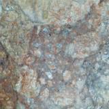 Dacita con alteración hidrotermal (detalle de la anterior) Escombrera del Cerro de San Cristóbal, Mazarrón (España) 20X Se observa la misma textura de vitrófido, ahora con pigmentaciones en tonos rojizos y ocres. (Autor: prcantos)