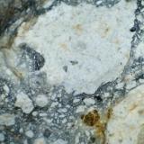 Dacita (detalle de la anterior) Escombrera del Cerro de San Cristóbal, Mazarrón (España) 20X Se aprecian granos pequeños de cuarzo de color oscuro dentro de los feldespatos blancos. (Autor: prcantos)