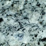 Riodacita (detalle de la anterior) Mazarrón (Murcia, España) 20X Cuarzo (grano grisáceo irregular en la zona superior, y otros menores), feldespatos blancos, escamas negras de biotita y un grano azulado de cordierita. (Autor: prcantos)