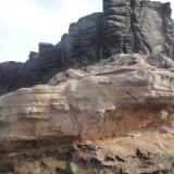 Estratos de toba soportando una colada basáltica La Isleta, Gran Canaria, España Como referencia, salen los muslos de una señora en el extremo inferior derecho (Autor: María Jesús M.)