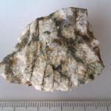 Charnockita Nelson County (Virginia, EEUU) Roca con textura de grano grueso (incluso pegmatítica) con cuarzo (grano gris en la parte superior), grandes feldespatos blancos y piroxeno oscuro en vetas. (Autor: prcantos)