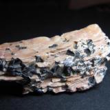 Esquisto de cloritoide Lago Grubependity, Urales Subpolares, República Kumi, Rusia 5x2'5 cm. Plaquetas negras de cloritoide en matriz rosada rica en mica, con fina esquistosidad. (Autor: prcantos)