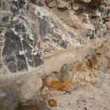 Magnesita-esmectita, cubierta de negro por óxidos de manganeso. Barranco de Guanarteme. Las Palmas de Gran Canaria. España. Altura aproximada unos 1 metro. En este caso, la magnesita-esmectita está sobre un conglomerado volcánico, con grandes bloques de roca rubefactada. (Autor: María Jesús M.)