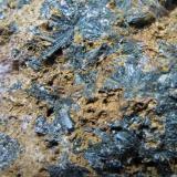 Pegmatita sienítica de aegirina (detalle) Dehnel's pit, Complejo plutónico de Stettin, Condado Marathon, Wisconsin, Estados Unidos Ancho de campo: 4 cm. Detalle de las rosetas de aegirina.  La matriz está visiblemente alterada. (Autor: prcantos)