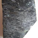 Nuumita (cara pulida) Nuuk, Kitaa, Groenlandia 6'5 x 5 cm. Nuumita es el nombre común de una roca metasomática formada por los anfíboles antofilita y gedrita.  Los cristales son alargados y dan cierto carácter orientado a la estructura de la roca.  Se observan bonitas irisaciones que hacen la roca muy atractiva, sobre todo en planchas pulidas (de hecho, no es fácil encontrar ejemplares sin pulir). (Autor: prcantos)