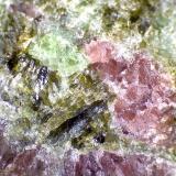 Eclogita Åheim, Vanylven, Møre og Romsdal, Noruega 60X Un cristal acicular oscuro, quizá anfíbol, y otros de color oliváceo, quizá clinozoisita. (Autor: prcantos)