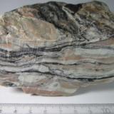 Milonita Noruega 10 x 4'5 cm. (sección transversal) x 9 cm. Una tectonita bien desarrollada de composición cuarzo-feldespática.  En primer plano se observa la sección transversal (se perciben marcas de corte de la sierra), con su típica estructura debida a la deformación dúctil: las fases minerales de mayor competencia (almendras y nódulos cuarzofeldespáticos) están rodeadas por los minerales menos consistentes que fluyen a su alrededor (filosilicatos oscuros). (Autor: prcantos)