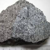 Essexita (gabro nefelínico) Crawfordjohn, South Lanarkshire, Escocia, Reino Unido 9 x7 cm. La essexita es una variedad de monzogabro nefelínico (o monzodiorita nefelínica) con titanoaugita, kaersutita ± biotita, labradorita y cantidades menores de feldespato alcalino y nefelina.  En este ejemplar se aprecian cristales casi centimétricos de augita en una matriz azulada de grano más fino. (Autor: prcantos)